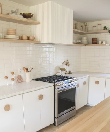 Modern cookspace with white flat panel kitchen cabinets and geometric pulls