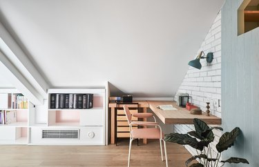 Scandinavian home office in the attic with brick wall and white storage unit