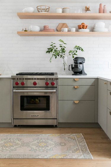 Modern cookspace with green beadboard flat panel kitchen cabinets