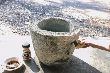 Applying coffee mixture to hypertufa planter with a sponge