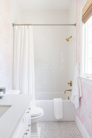 traditional shower fixtures with white wall tile and pink wallpaper