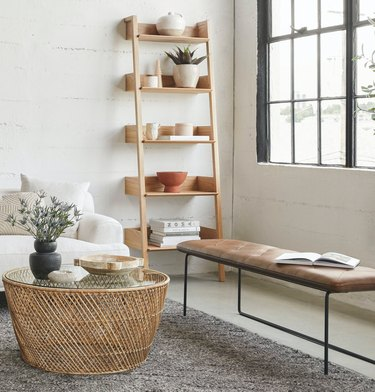 Bookshelves for Small Spaces with Bookcase, leather bench, wicker coffee table, rug, couch, flowers, vase, pottery.