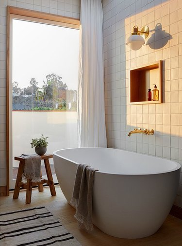 white bathroom with wood accents and brass tub fixtures