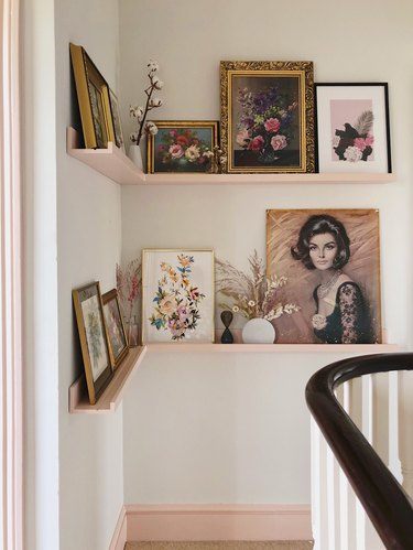 Hallway Makeover Ideas in pink and white hallway with corner picture ledge and vintage art
