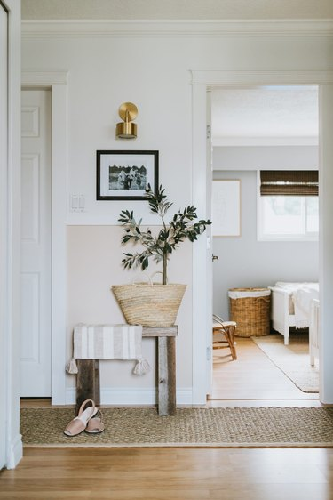 Hallway Makeover Ideas in two tone hallway with molding, wall lights and jute runner