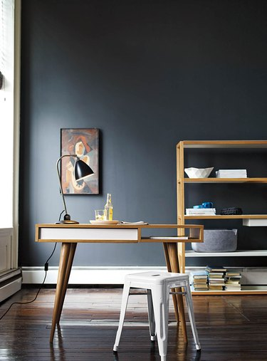 black home office with midcentury modern wooden furniture and large shelving unit in the back