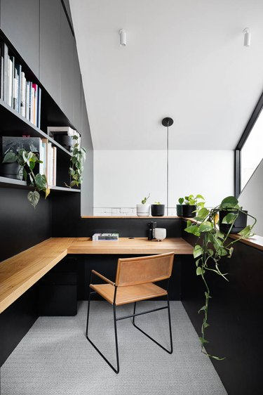 black home office in a landing nook with wood wall mount wrap-around desk