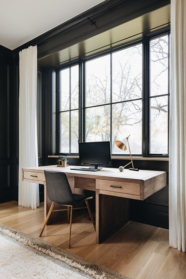 black home office with desk in front of windows