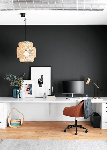 black home office with accent wall, woven light fixture hanging above the white wall-mount desk