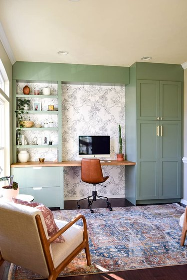 Green home office with green built-ins and black and white wallpaper