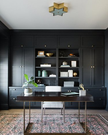 black home office with light wood floors, desk in the center of the room with a star-shaped pendant hanging above