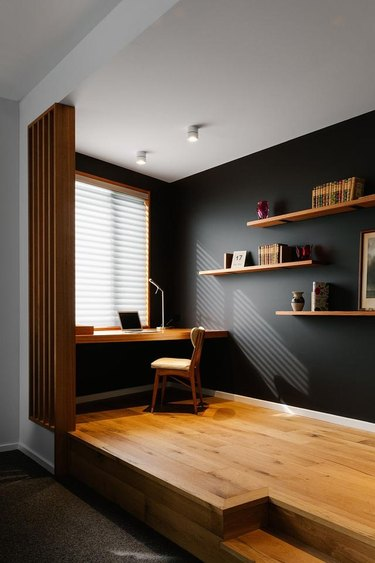 black and white home office with warm wood flooring and a desk sitting underneath a window