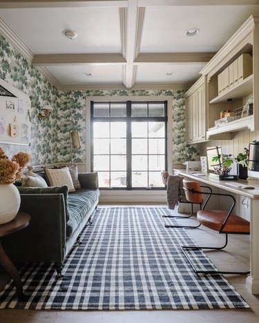 Green home office with patterned wallpaper and plaid area rug