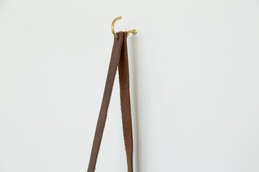 leather strap hanging from hook on wall