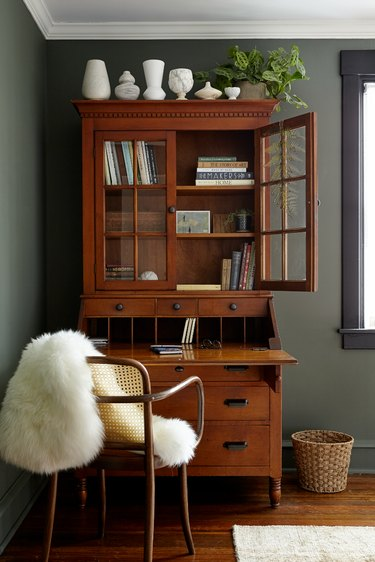 Green home office with vintage pieces and white faux fur
