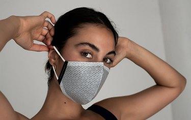 woman putting on KILLSPENCER SST Face Mask