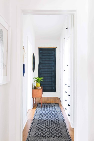 Hallway Focal Point Ideas in white hallway with vintage runner and boho wall tapestry