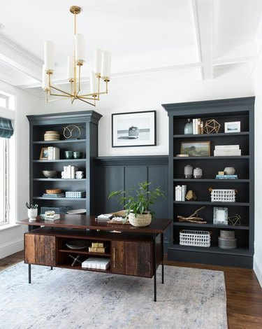 traditional home office with blue green built-ins and a brass chandelier
