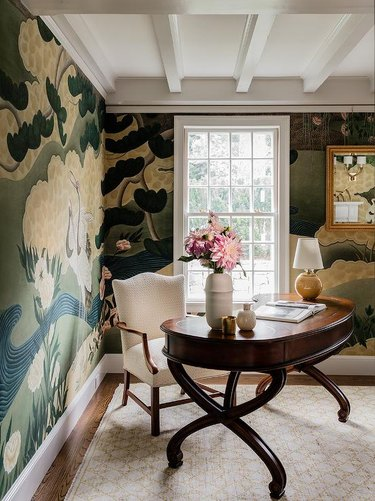 traditional home office with oval desk and mural wallpaper