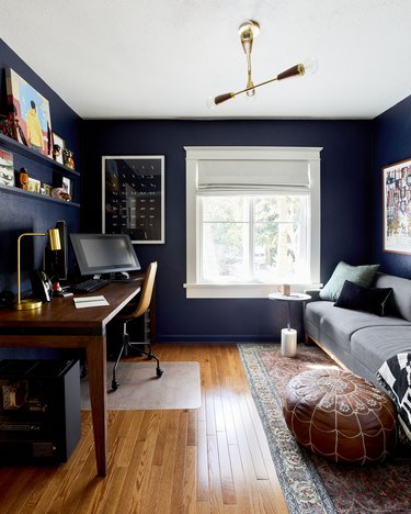 blue home office with midcentury decor and moroccan pouf