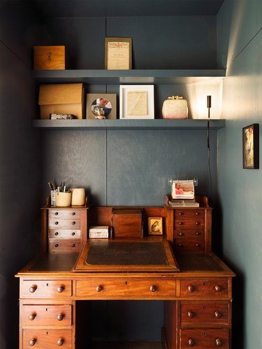 dark blue home office with an antique wooden desk