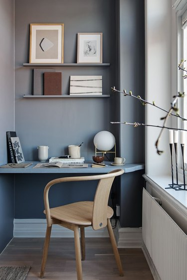 light blue home office in a corner nook with built in shelves
