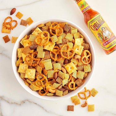 cravings by chrissy teigen White Cheddar Cholula Chex Mix on marble counter