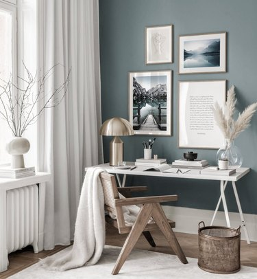 blue home office with an accent wall and white window treatments aside it