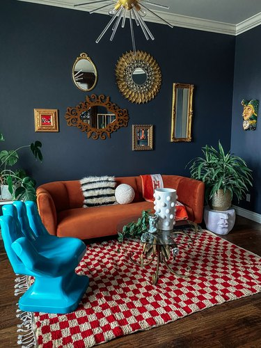 navy blue living room with burnt orange sofa