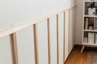 Nail the vertical slats to the wall.