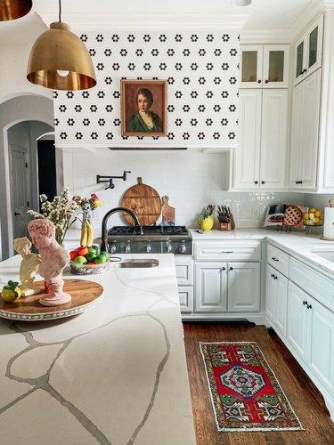 Sarisa Munoz The Indigo Leopard Home kitchen with white cabinets brass pendants