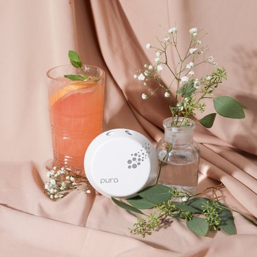 white plug-in diffuser with glass of juice and vase with flowers