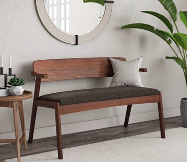 Hallway Benches with back, cushion, round mirror, side table, plant.