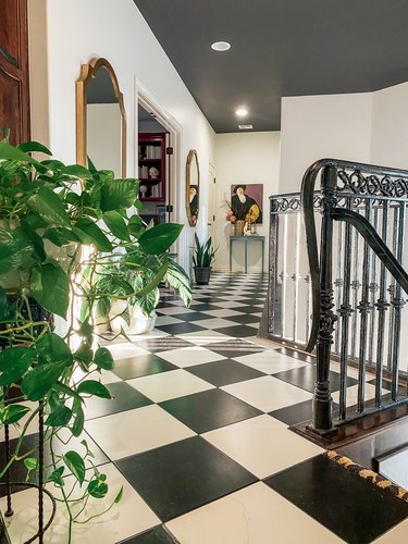 Sarisa Munoz The Indigo Leopard Home hallway with black and white checkered floor tile and potted plants