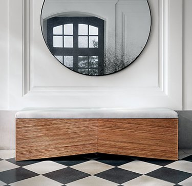 Rattan Hallway Benches with cushion, round mirror, black and white floors.