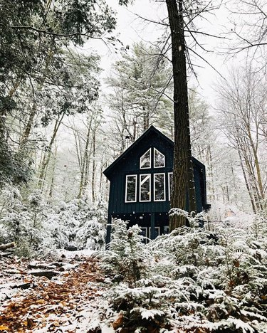 snowy outdoor scene with view of a black a-frame house