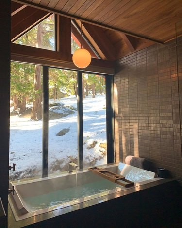 bath tub with view of trees and snowy scene