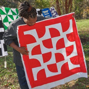 woman holding black and white quilt