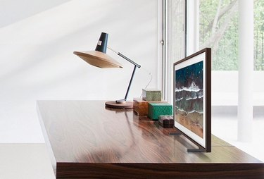 samsung frame tv on dresser with table lamp and storage boxes