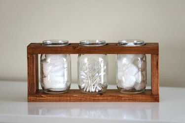mason jar for bathroom storage in wood caddy with cotton balls and Q-tips