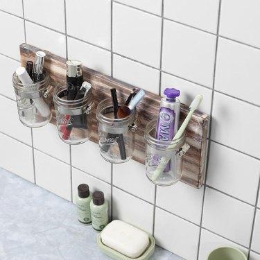 mason jar for bathroom storage mounted to white tile wall