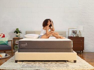woman sitting on cocoon by sealy memory foam mattress