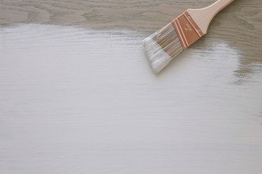 paintbrush and partially painted wood surface