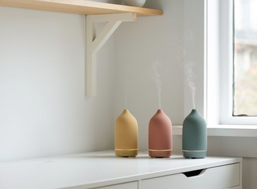 three essential oil diffusers in varying colors on top of a white piece of furniture near window