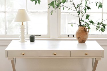 Home office desk painted with light gray milk paint in front of window with lamp and vase