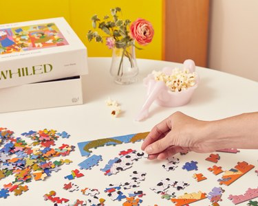 whiled puzzle being assembled on white table with puzzle box, flower, and popcorn tray