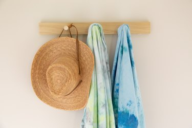 Tie-dyed towels hanging on wood peg rack with hat