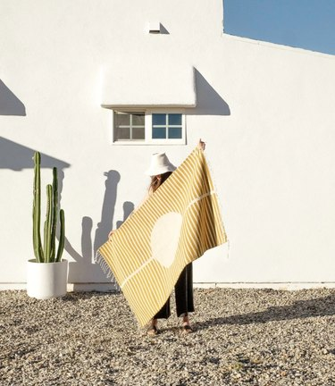Woman standing with yellow and white striped eco-friendly rug in desert scene