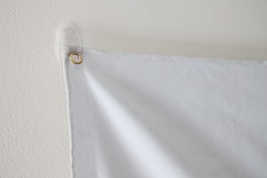 Projector screen hanging on adhesive wall hook