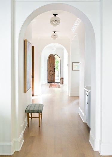 Hallway Pendant Light in White hallway with wood floors, ceramic pendants, bench, art.